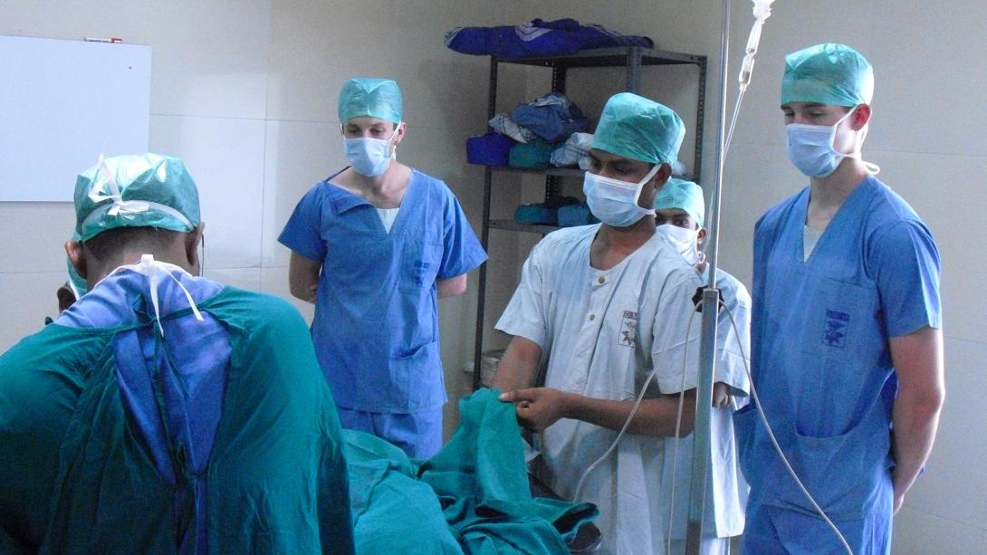 Medical interns observe local doctors performing surgery in India.
